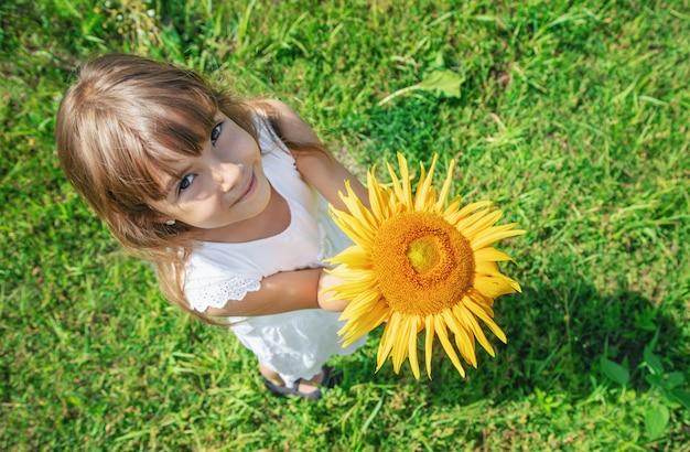 Uma criança em um campo de girassóis.