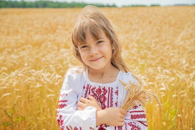 Uma criança em um campo de trigo em uma camisa bordada.