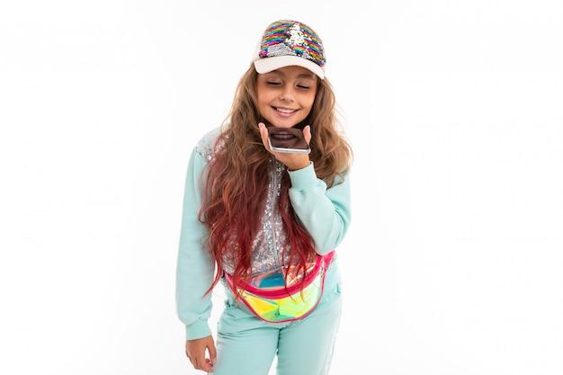 Uma criança em um elegante agasalho falando no viva-voz, segurando um smartphone nas mãos com a tela para cima