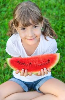 Uma criança em um piquenique come melancia