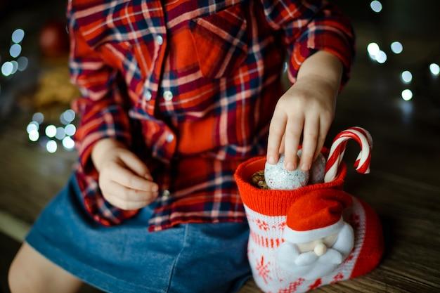 Uma criança em uma camisa vermelha quadriculada leva doces de um doce presente de natal