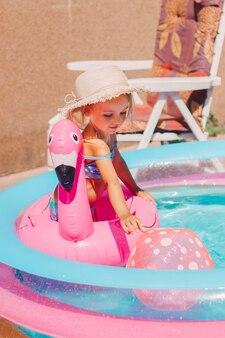 Uma criança em uma piscina inflável se banha no quintal de chapéu e maiô