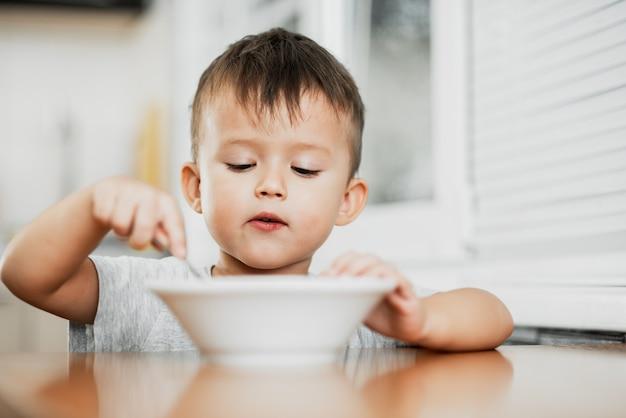 Uma criança encantadora com uma camiseta na cozinha come mingau de aveia com muita avidez