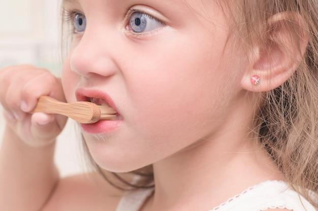 Uma criança escova os dentes com uma escova de dentes de bambu