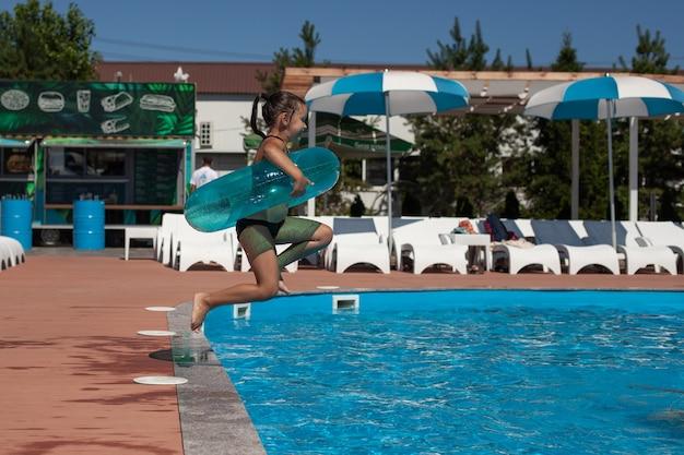 Uma criança está brincando no parque aquático. a menina feliz pula na piscina e se põe de inflar ...