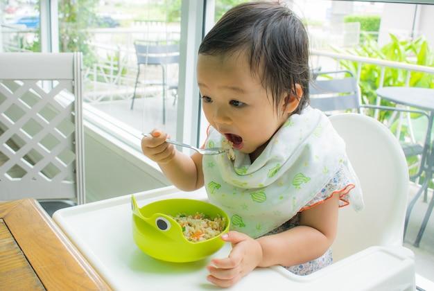 Uma criança está comendo sozinha com colher. bebê comendo.