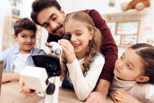 Uma criança está olhando através de um microscópio.