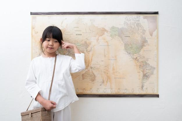 Uma criança está pensando na frente do mapa do mundo.