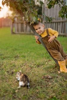 Uma criança está perto de uma árvore e olha para um pequeno gatinho sem-teto