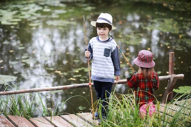 Uma criança está pescando na manhã de outono. pôr do sol de outono na lagoa. um pescador com uma vara de pescar na passarela.