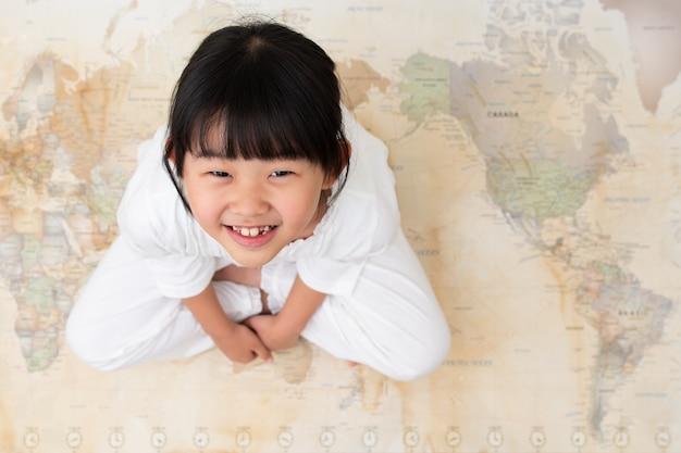 Uma criança está sentada em um mapa do mundo.