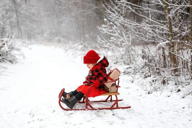 Uma criança está sentada na floresta em um trenó com presentes de natal decorados com fitas