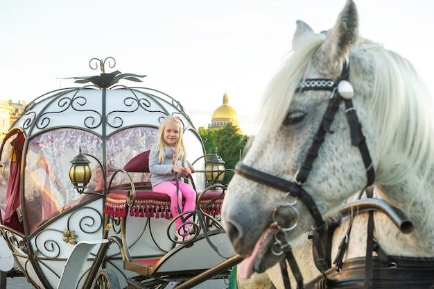 Uma criança está sentada no banco do motorista em uma velha carruagem na palace square, em são petersburgo