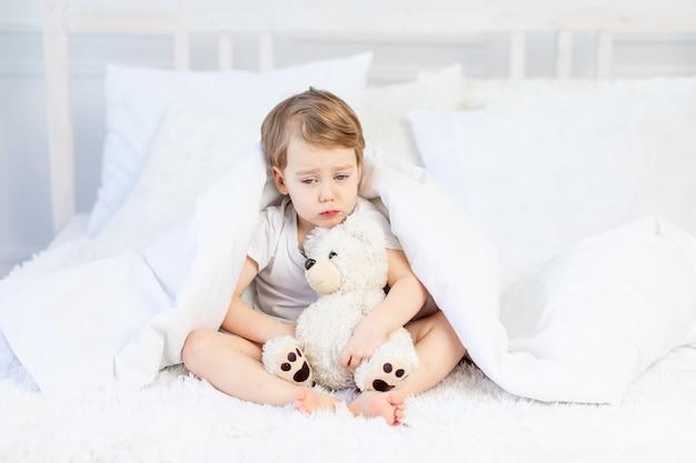 Uma criança está triste com um ursinho de pelúcia na cama em casa