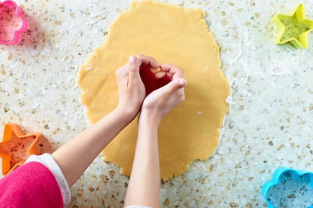 Uma criança faz biscoitos, estende a massa e usa formulários para fazer biscoitos.