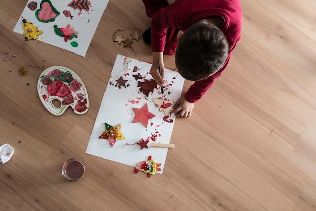 Uma criança fazendo decorações de pintura de natal