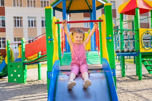Uma criança feliz brinca no parque infantil do complexo infantil perto de casa no verão no quintal e sorri