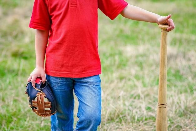 Uma criança feliz com taco de beisebol no conceito de natureza no parque