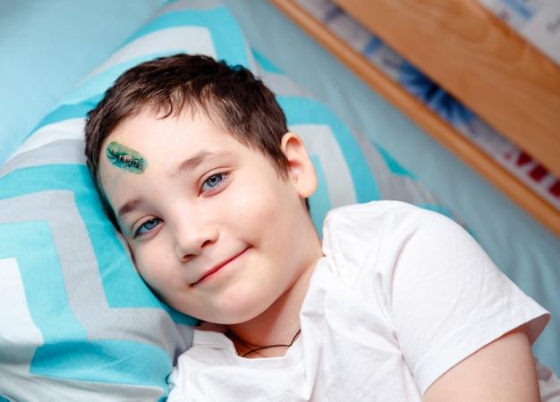 Uma criança feliz com um ferimento na cabeça está deitada na cama e aguardando o exame médico em casa.