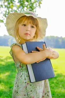 Uma criança feliz com um livro sobre a natureza da bíblia no parque