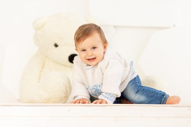Uma criança feliz de seis meses com uma jaqueta quente de tricô e jeans rasteja em casa perto de um grande ursinho de pelúcia