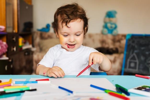 Uma criança feliz e alegre desenha em um álbum com uma caneta de feltro usando uma variedade de ferramentas de desenho.