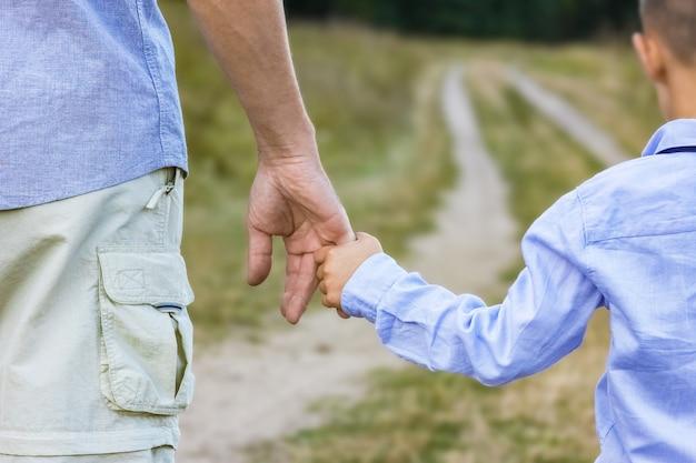 Uma criança feliz e as mãos dos pais na natureza na viagem do parque