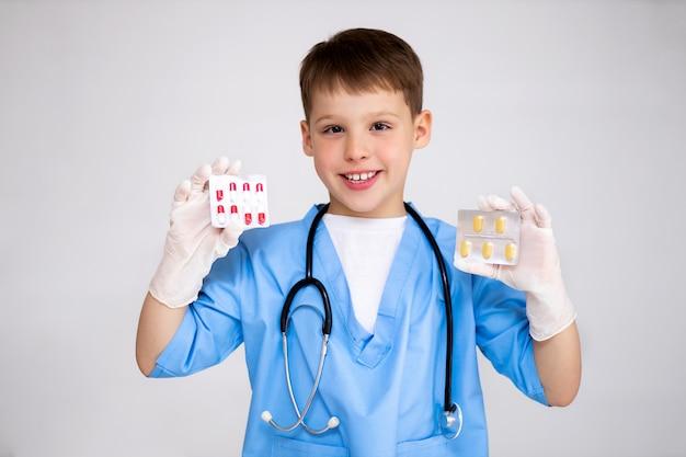 Uma criança feliz em um terno de médico com um estetoscópio no pescoço em luvas médicas detém comprimidos multicoloridos nas mãos e sorri com dentes brancos.