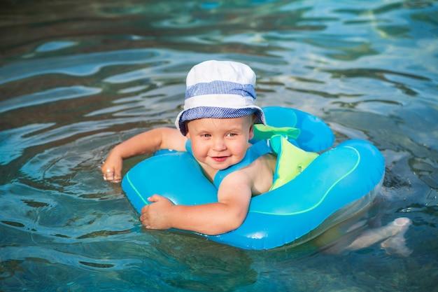 Uma criança feliz nada em um anel de natação no mar adriático, montenegro
