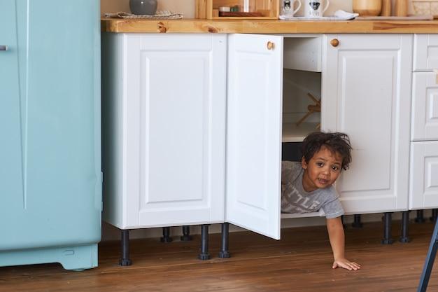 Uma criança feliz parece fora do armário na cozinha