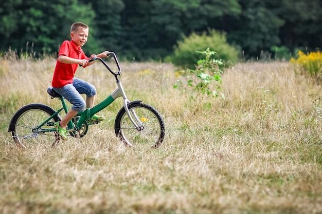 Uma criança feliz pedalando no conceito de parque na natureza