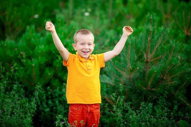 Uma criança feliz, um menino com roupas laranja fica parado na grama verde no verão e levanta as mãos
