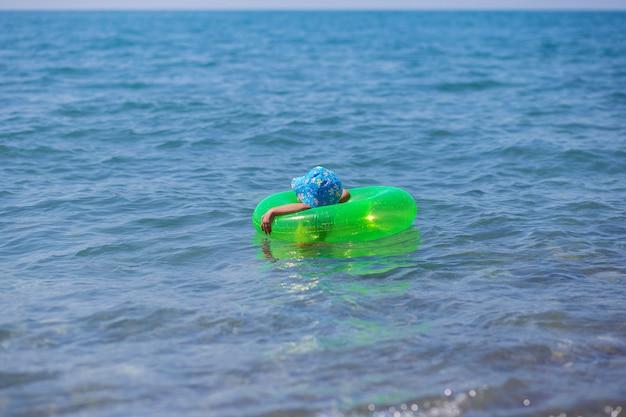 Uma criança flutua sozinha em um anel de borracha no meio do mar