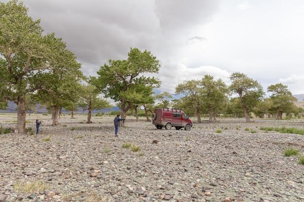 Uma criança fotografa um pai que fotografa um carro no fundo das montanhas da mongólia