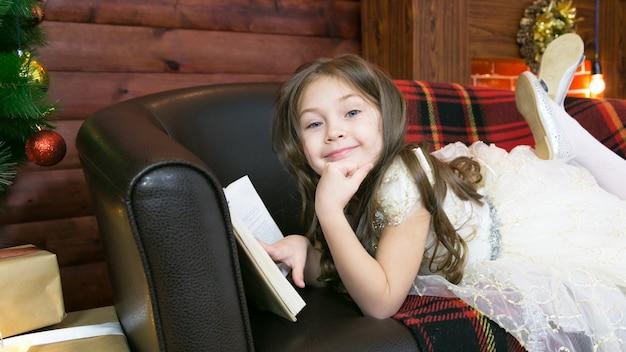 Uma criança lê um livro interessante ao lado da árvore de natal.