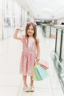 Uma criança linda no shopping faz compras. conceito de compras on-line. uma garota em um vestido rosa com sacos de pastel multicoloridos nas mãos