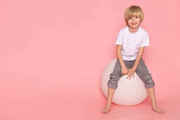 Uma criança loira vista frontal em t-shirt branca e calça jeans cinza, jogando com bola branca no espaço rosa