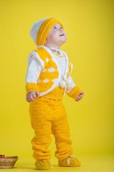 Uma criança menina de um ano com roupas amarelas olhando para cima em um fundo amarelo expressa emoções