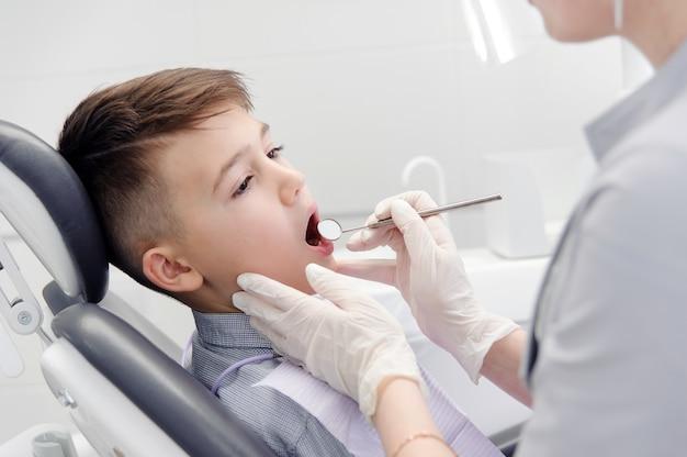 Uma criança menino com um dentista em um consultório odontológico