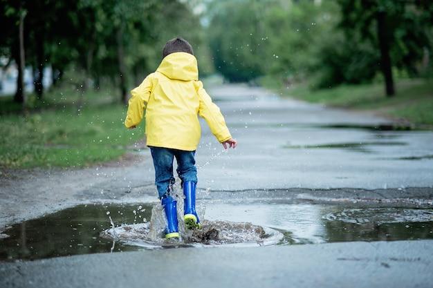 Uma criança molhada está pulando em uma poça. diversão na rua. revenimento no verão