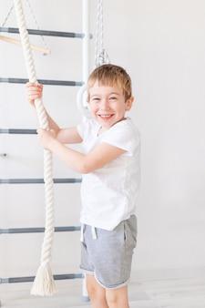 Uma criança na parede sueca pratica esportes em casa, um menino sobe na corda bamba, o conceito de esporte e saúde