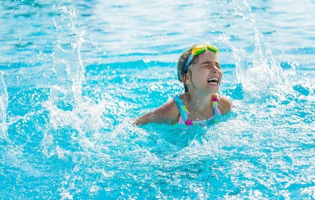Uma criança na piscina espirra água. foco seletivo. criança.