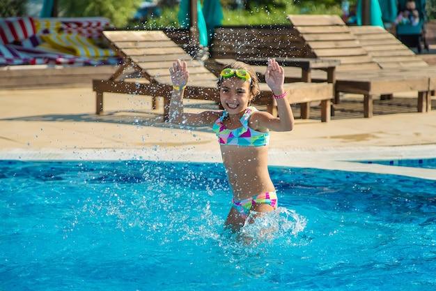 Uma criança na piscina espirra água. foco seletivo.