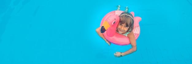 Uma criança nada em uma piscina com flamingo de borracha