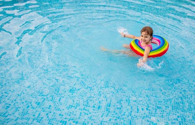 Uma criança nada em uma piscina com um colete salva-vidas.