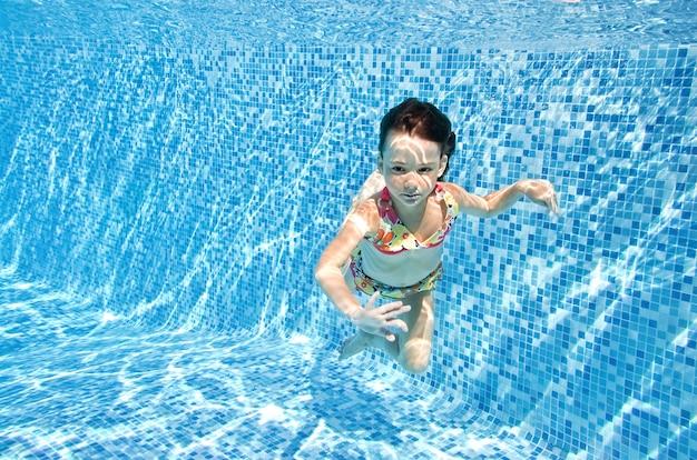 Uma criança nadando debaixo d'água na piscina, uma menina feliz e ativa mergulha e se diverte debaixo d'água