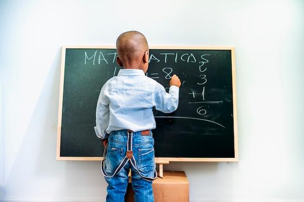 Uma criança negra escrevendo em um quadro negro