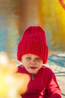 Uma criança no outono no parque chora em um casaco e um chapéu vermelho quente.