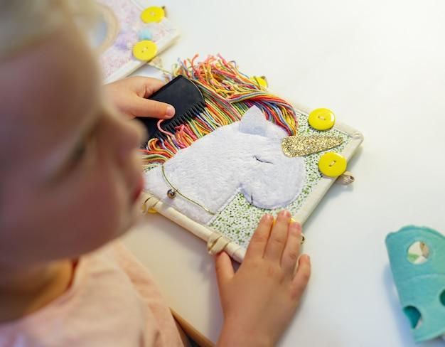 Uma criança penteia unicórnio branco feito de feltro