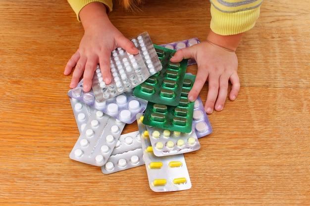 Uma criança pequena brincando com remédios.